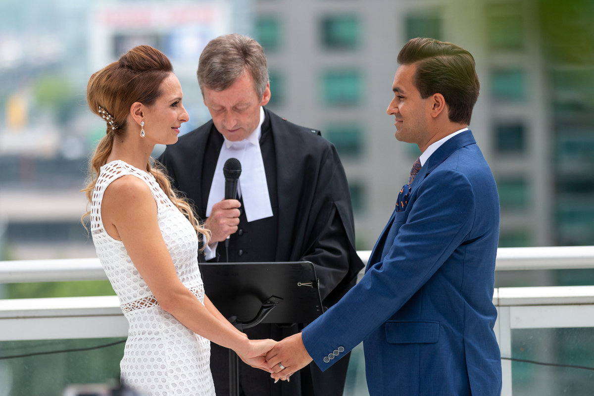 Bride and groom hold hands on a Toronto Rooftop Ceremony while they take their wedding vows