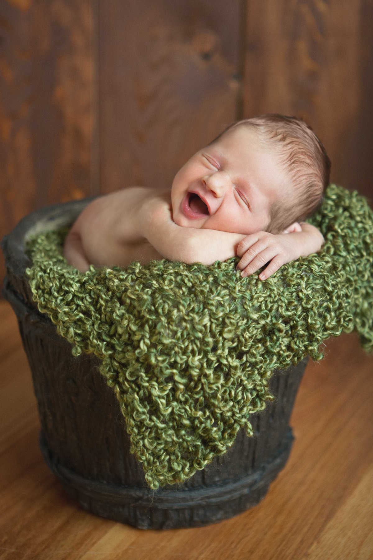 smiling newborn baby in a bucket prop from New Paltz by Hudson Valley professional photographer Cornwall NY photography studio