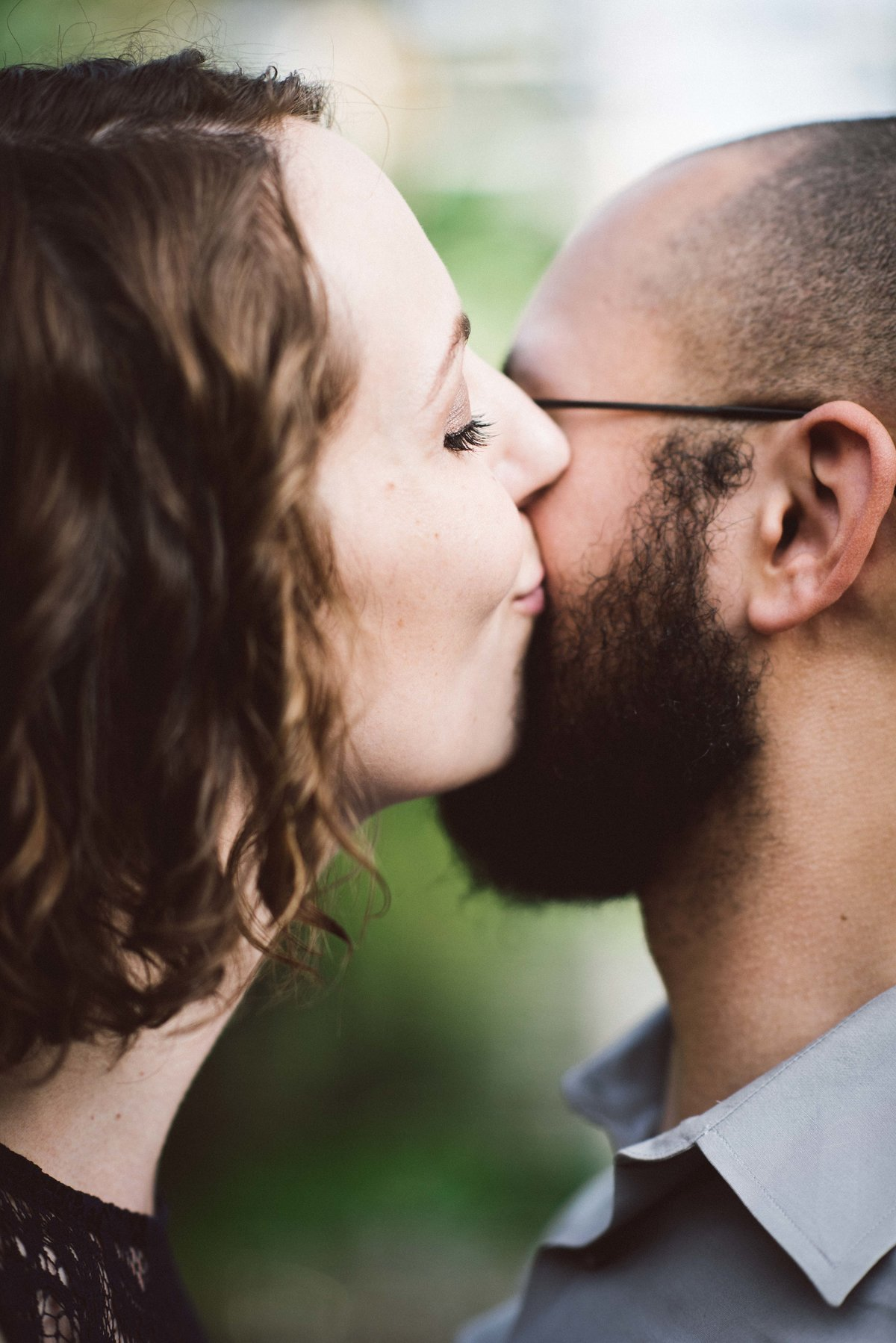 Woman kisses fiance during engagement session, Chicago.