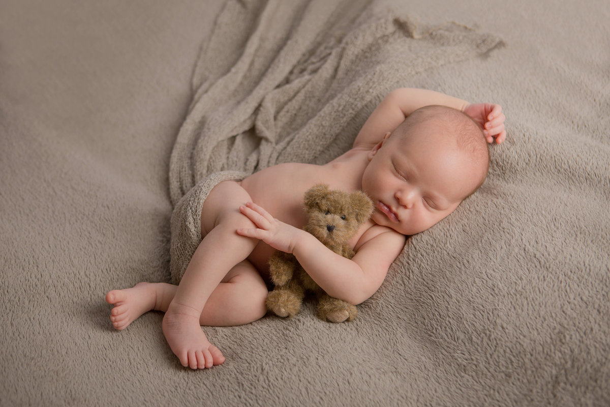 sweet simple newborn baby photo of Haverstraw in Rockland County snuggling with teddy bear in the Hudson Valley by professional photographer Autumn Photography in Cornwall NY photo studio