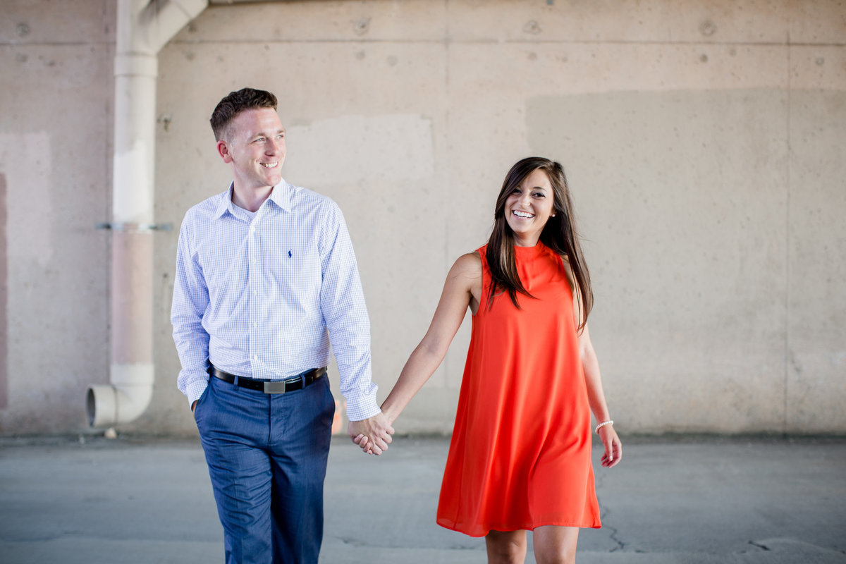 Walking towards the camera at Jackson Terminal Wedding Venue engagement photo by Knoxville Wedding Photographer, Amanda May Photos.