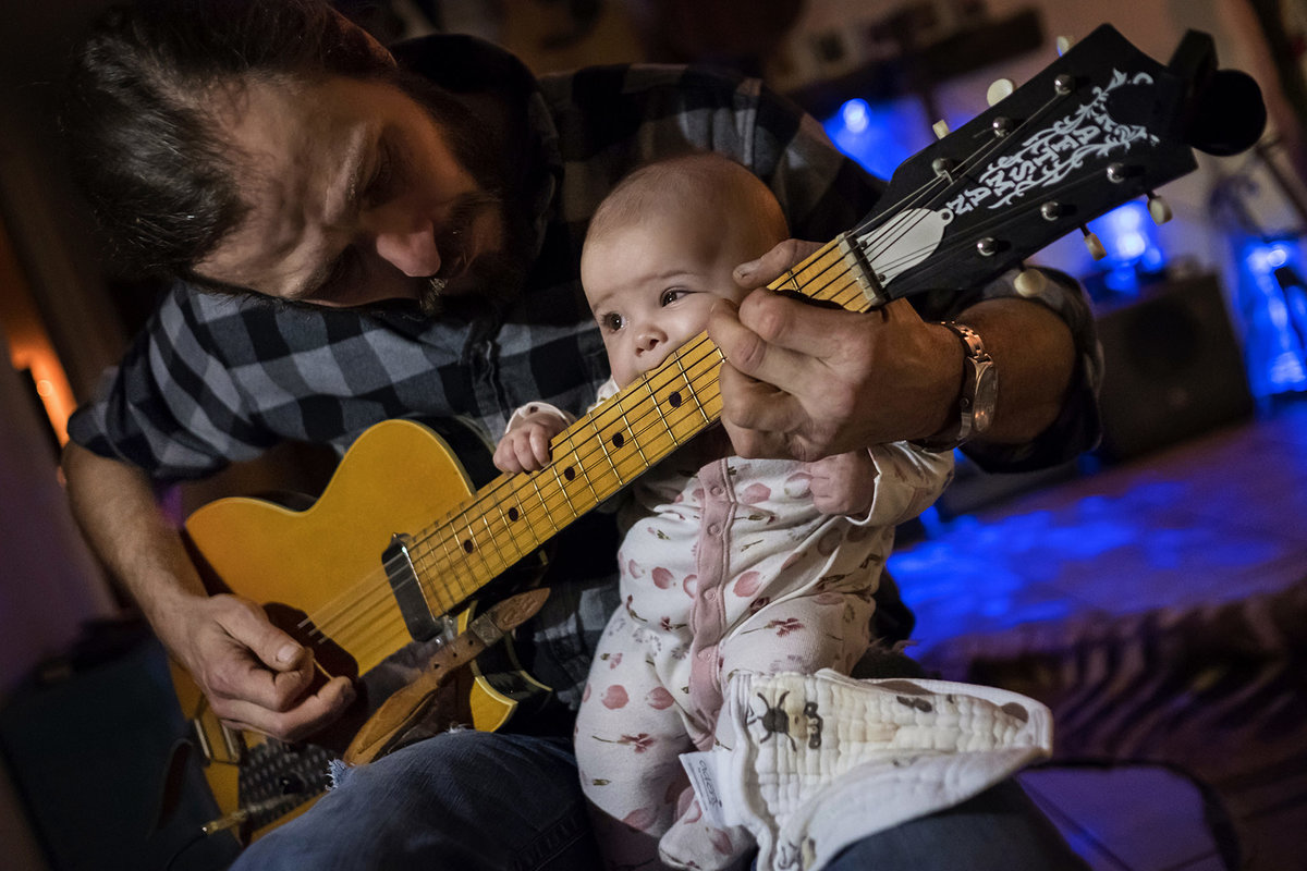 Newborn with musician father and guitar by King and Fields Studios Charleston SC