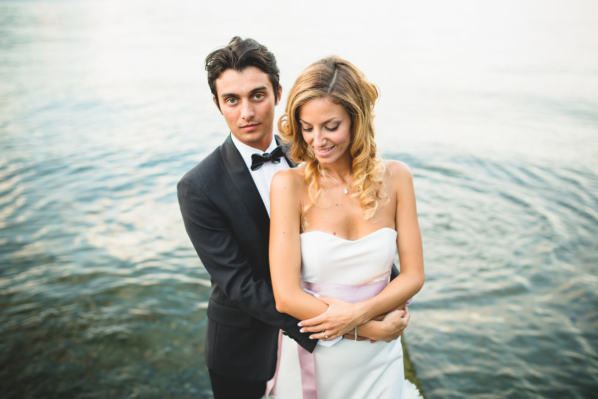 couple at lake como in front of the water. groom wears a bow tie