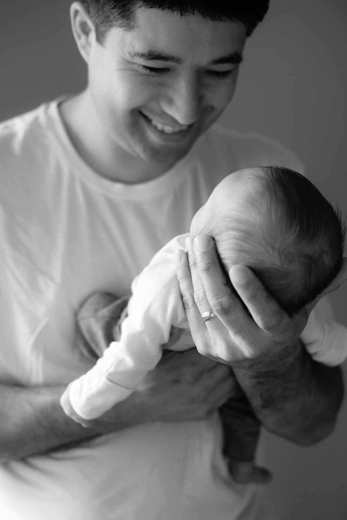 Black and white photo of dad holding his son suspended from his chest.  Dad is smiling staring back down at his baby boy.