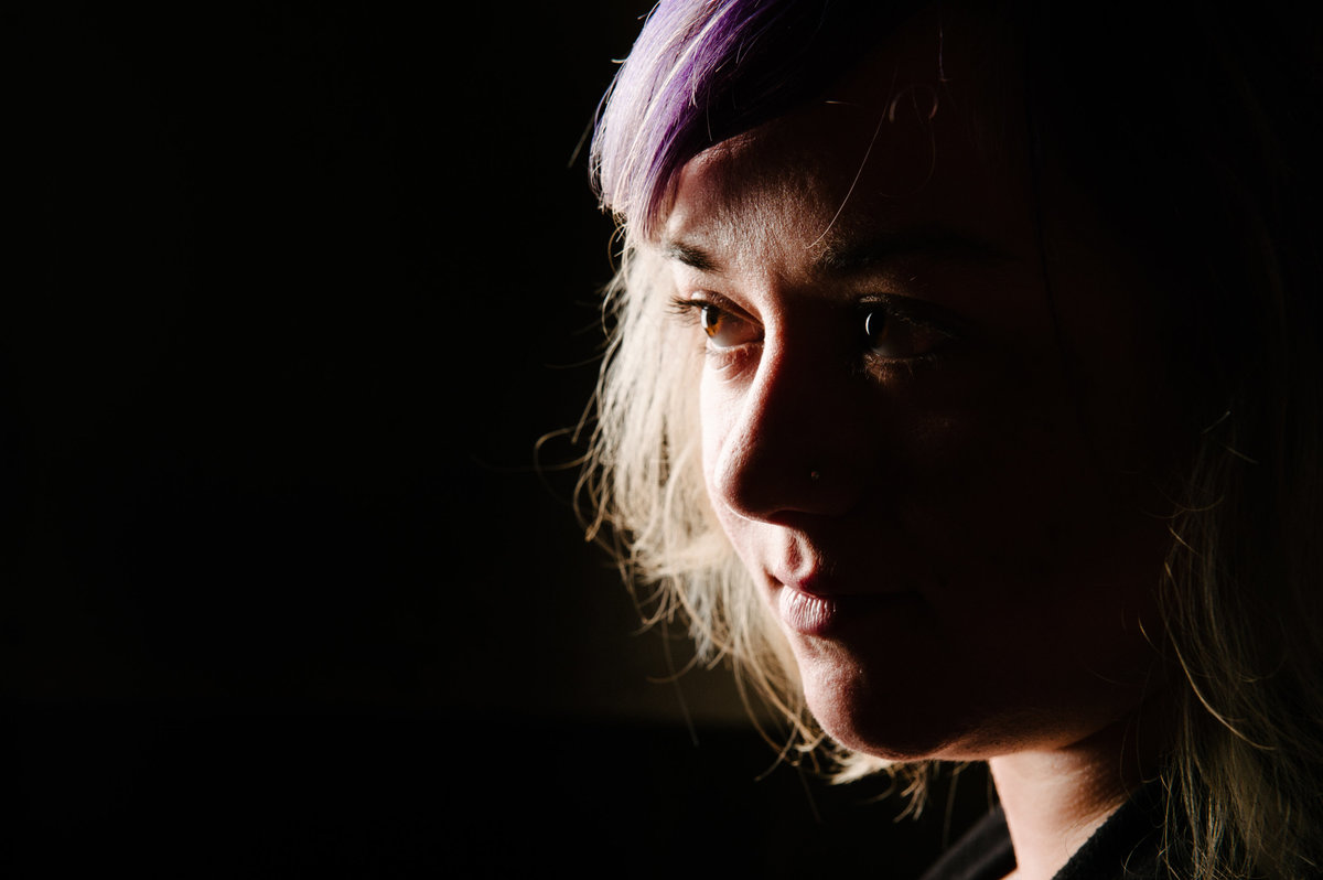 Chicago portrait, profile of woman with purple hair. backlight.