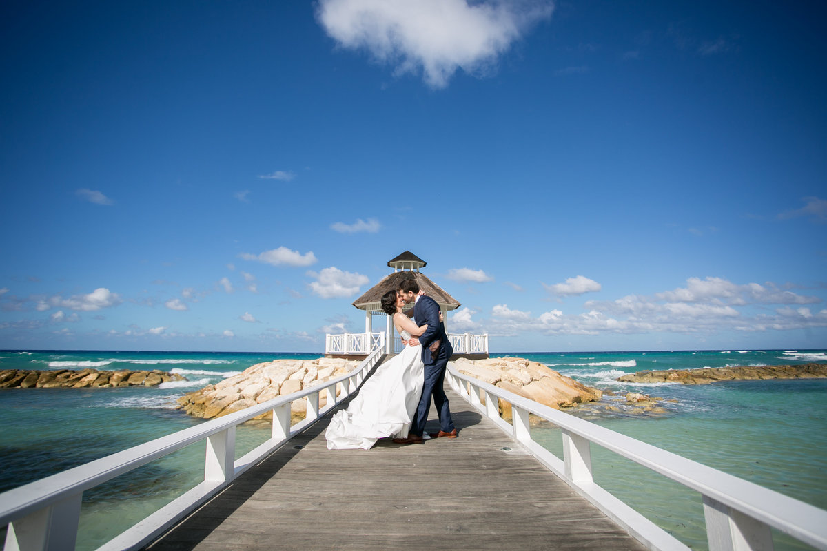 Bride and groom kissing on a dock in Jamaica