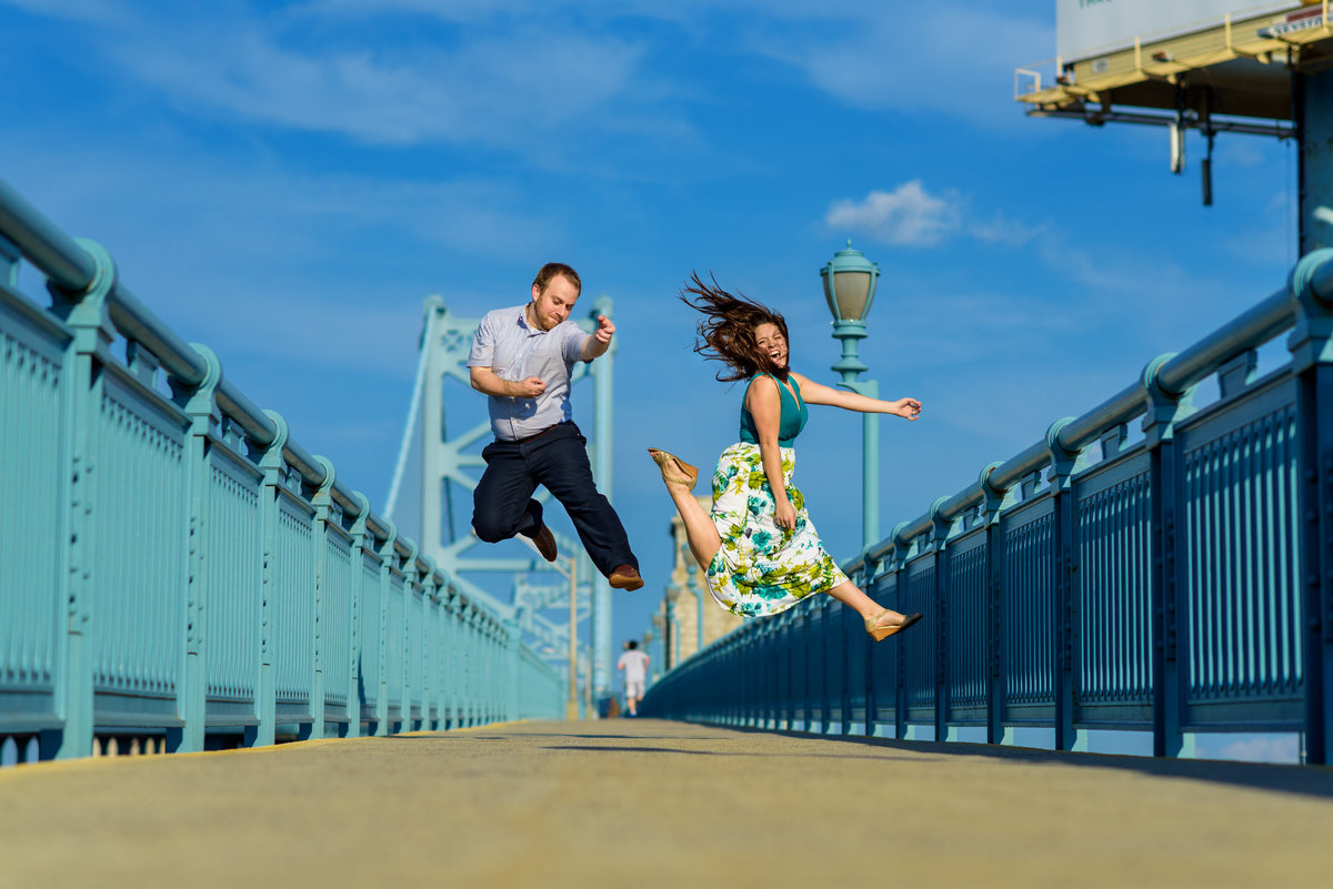 A fun couple playing air guitar on the ben franklin Bridge.
