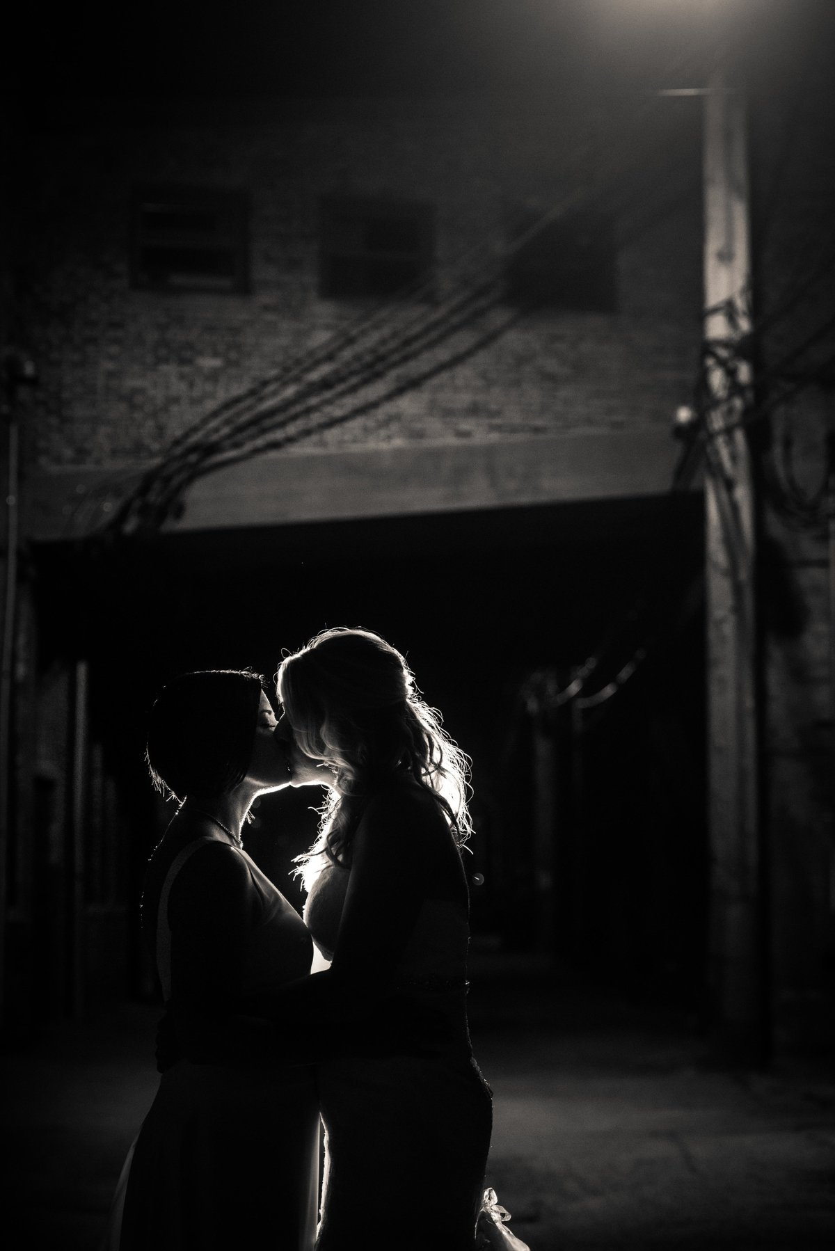 Brides in silhouette, urban background, kiss against backlight, Chicago.
