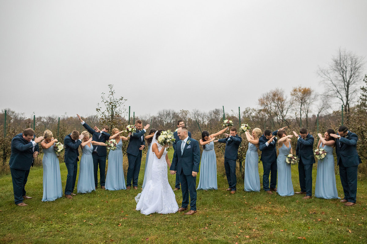 bridal party doing the dab with embarrassed couple