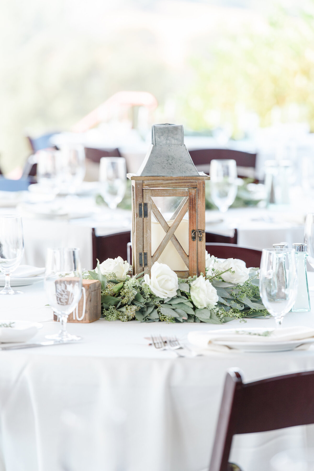 table with a wood lantern white flowers and greenery