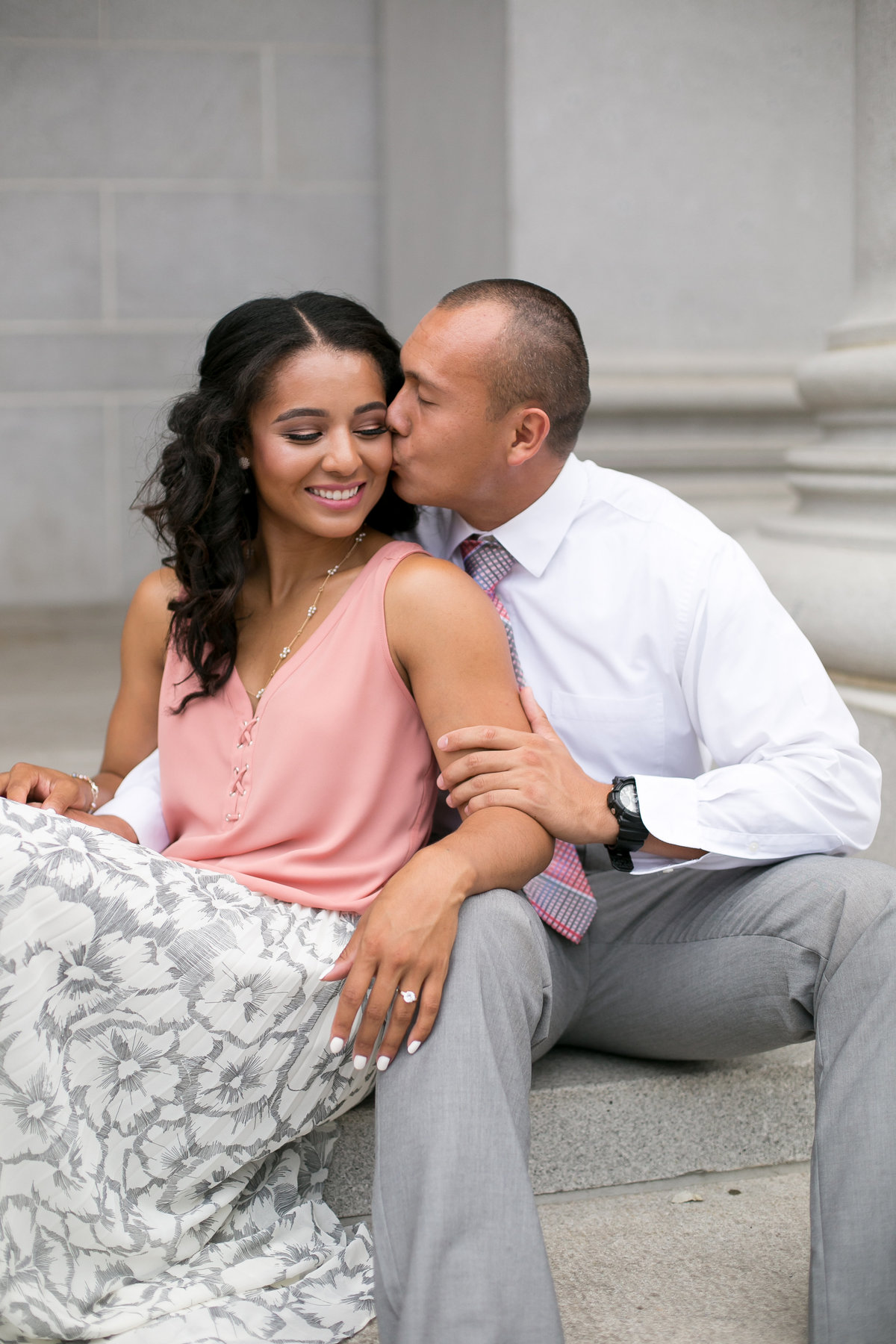 Couple sitting on steps, groom kissing bride's cheeck