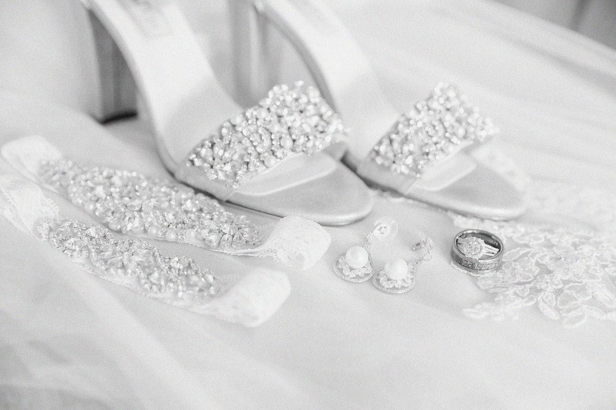 Brides shoes, garter, rings and earrings arranged together on wedding day in black and white