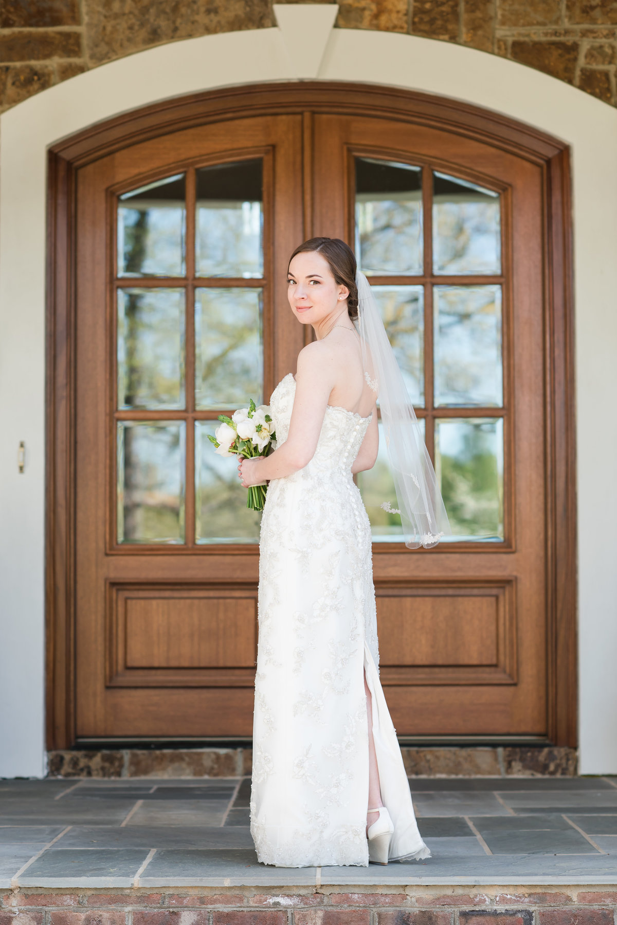 a bride wearing a laced strapless dress with no train with a mid-length veil standing on a gray bricked porch looking at the camera standing in front of a double wooden front door in Burlington