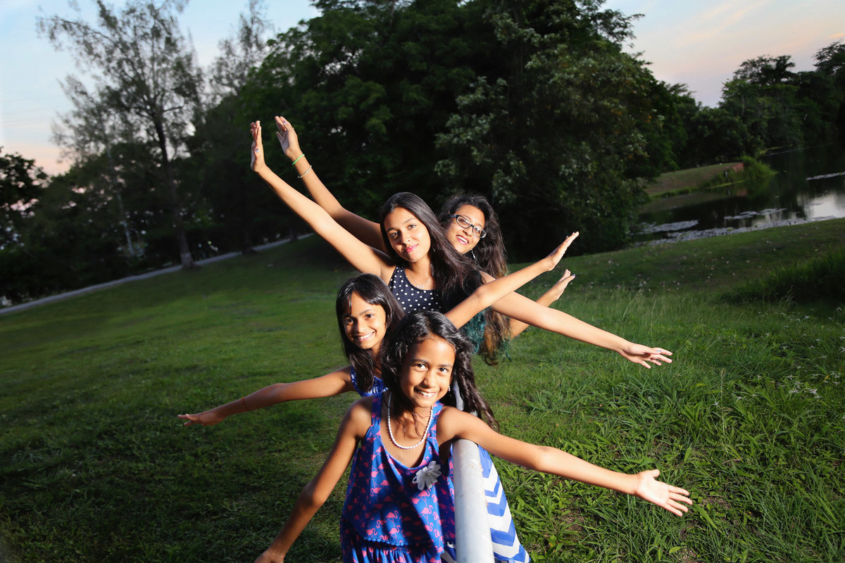 young girls in playful pose with outstretched hands in park. Photo by Ross Photography, Trinidad, W.I..