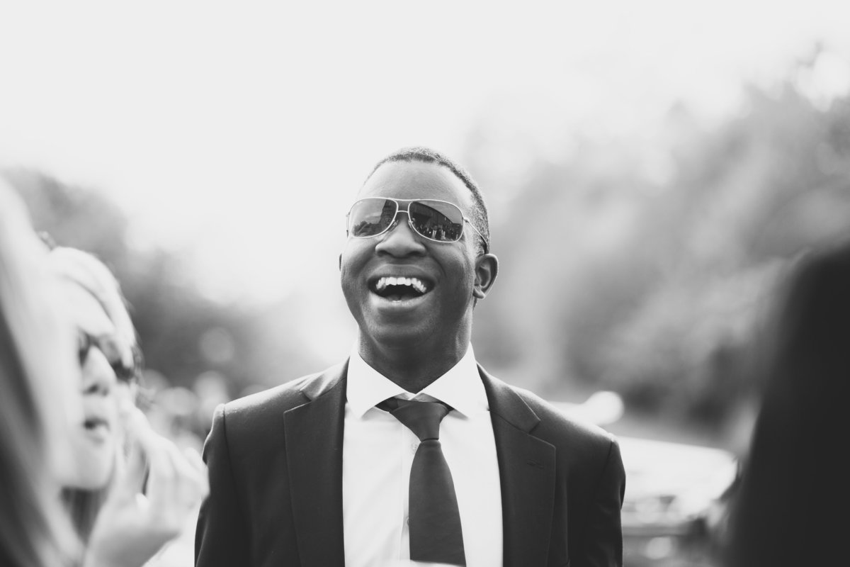 man laughing with sunglasses on at wedding