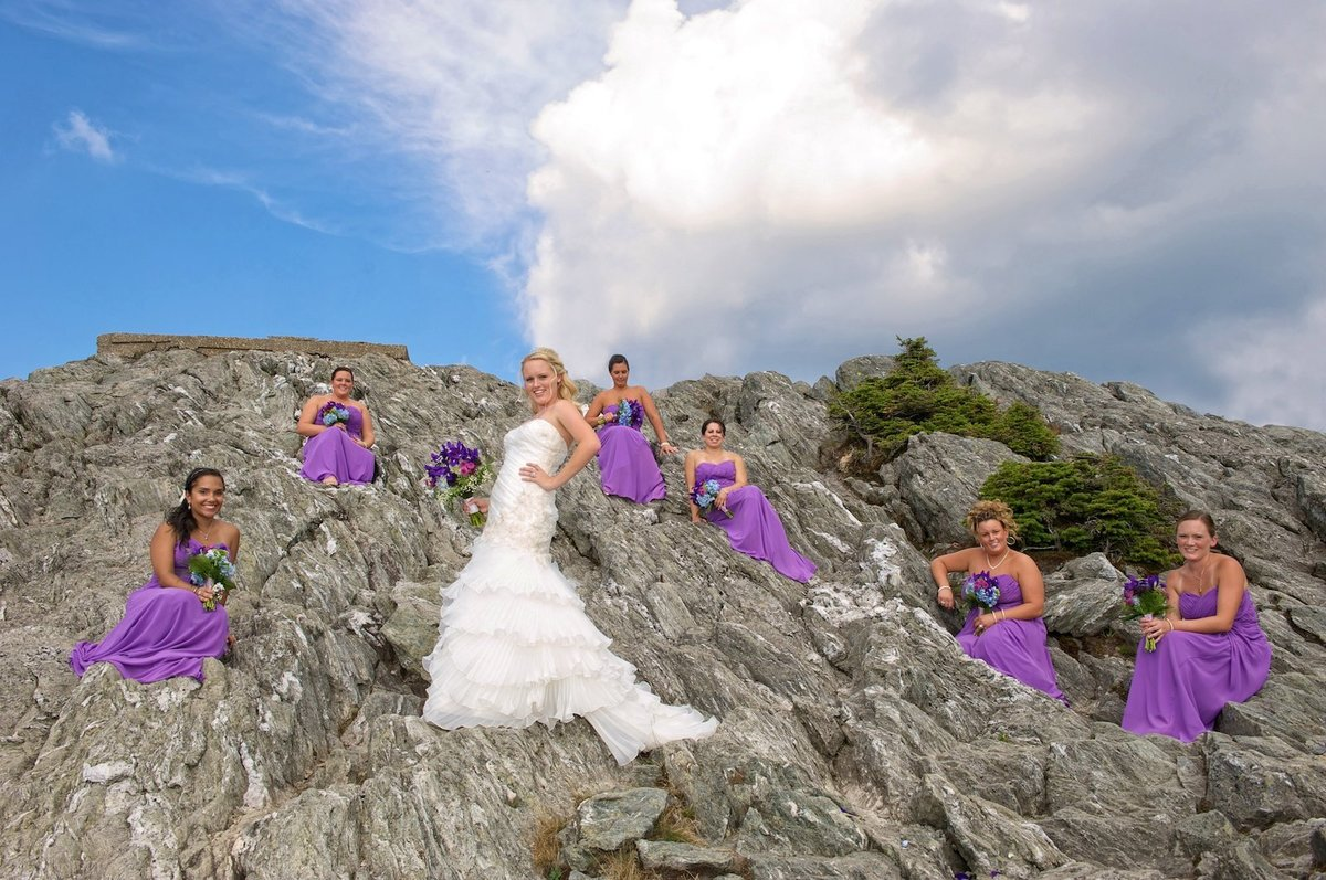 bride and her bridesmaids dressed in purple on the rock at Jay Peak elevation