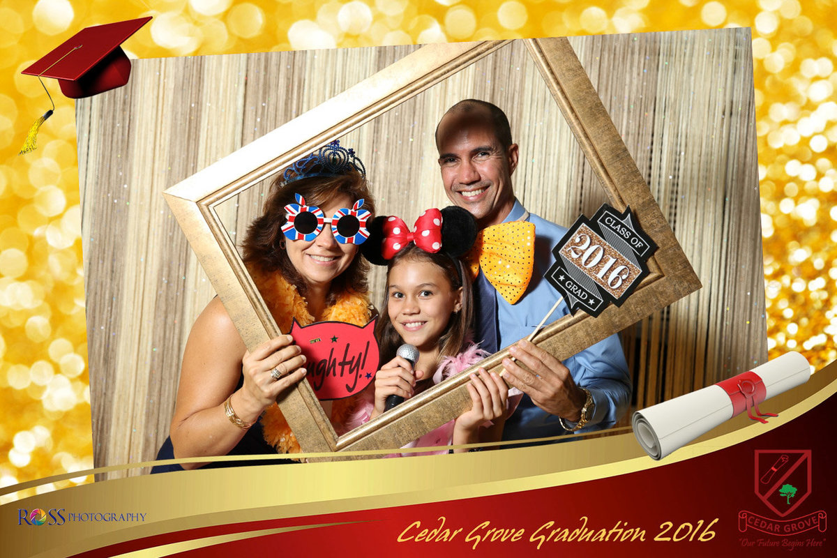 Man, woman, and little girl hold photobooth props. Photobooth by Ross Photography, Trinidad, W.I..
