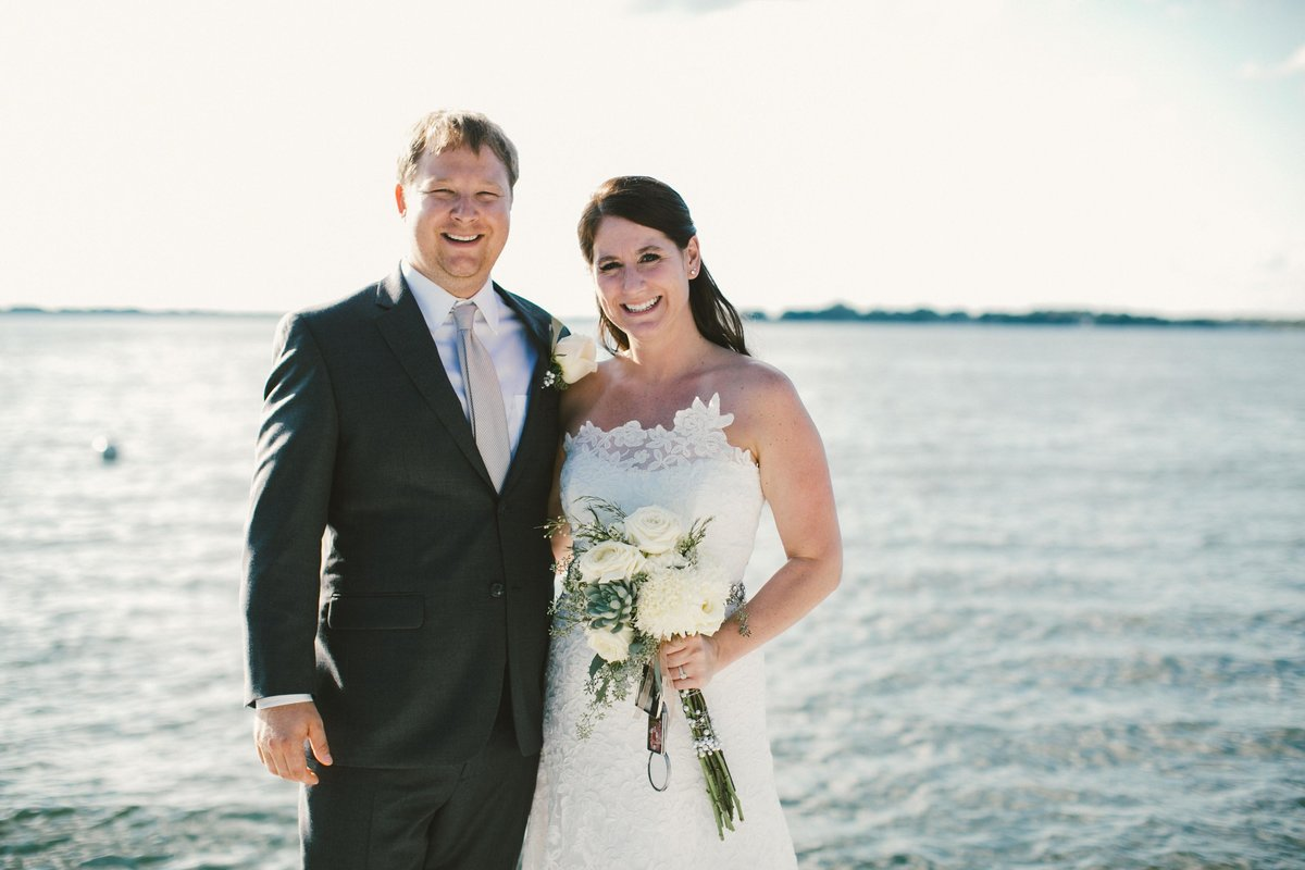 Couple stands in front of Lake Wawasee shortly after wedding ceremony