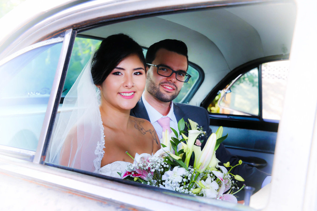 Bride and groom pose in wedding car. Photo by Ross Photography, Trinidad, W.I..
