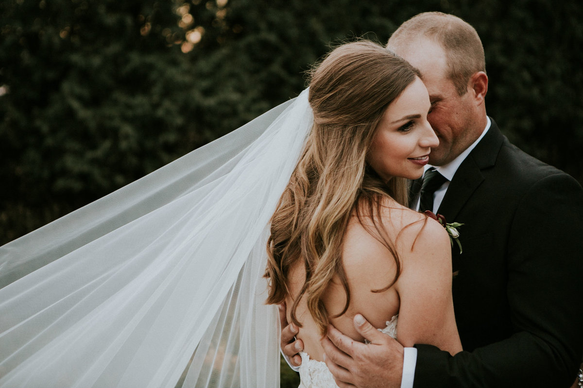 Couple embrace with veil flowing to left corner at Ritz Charles wedding