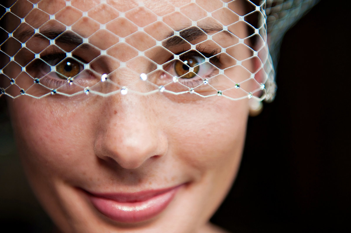 A beautiful bride in her birdcage veil before her rustic barn  wedding