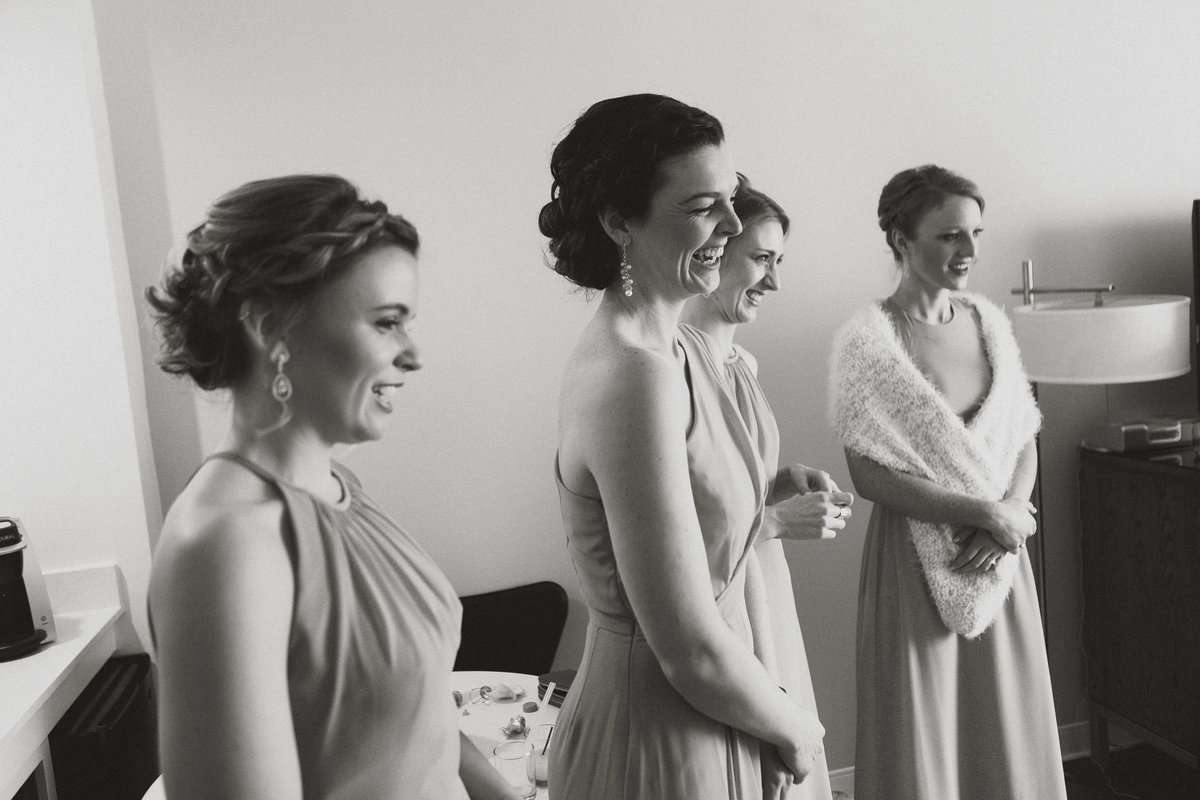 wedding party smiles while bride shows off her dress at Columbus wedding