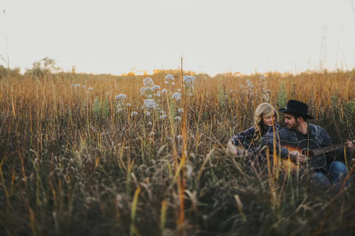 guy playing guitar for his girl in a field during their engagment photographs in rockford illinois
