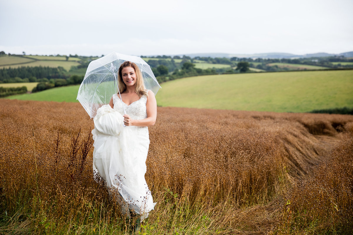 august wedding bride with brolly
