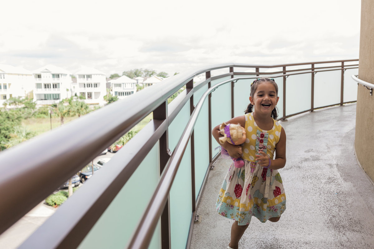 charlotte documentary photographer jamie lucido captures a day in the life of girl running down a hotel balcony at Myrtle Beach, North Carolina