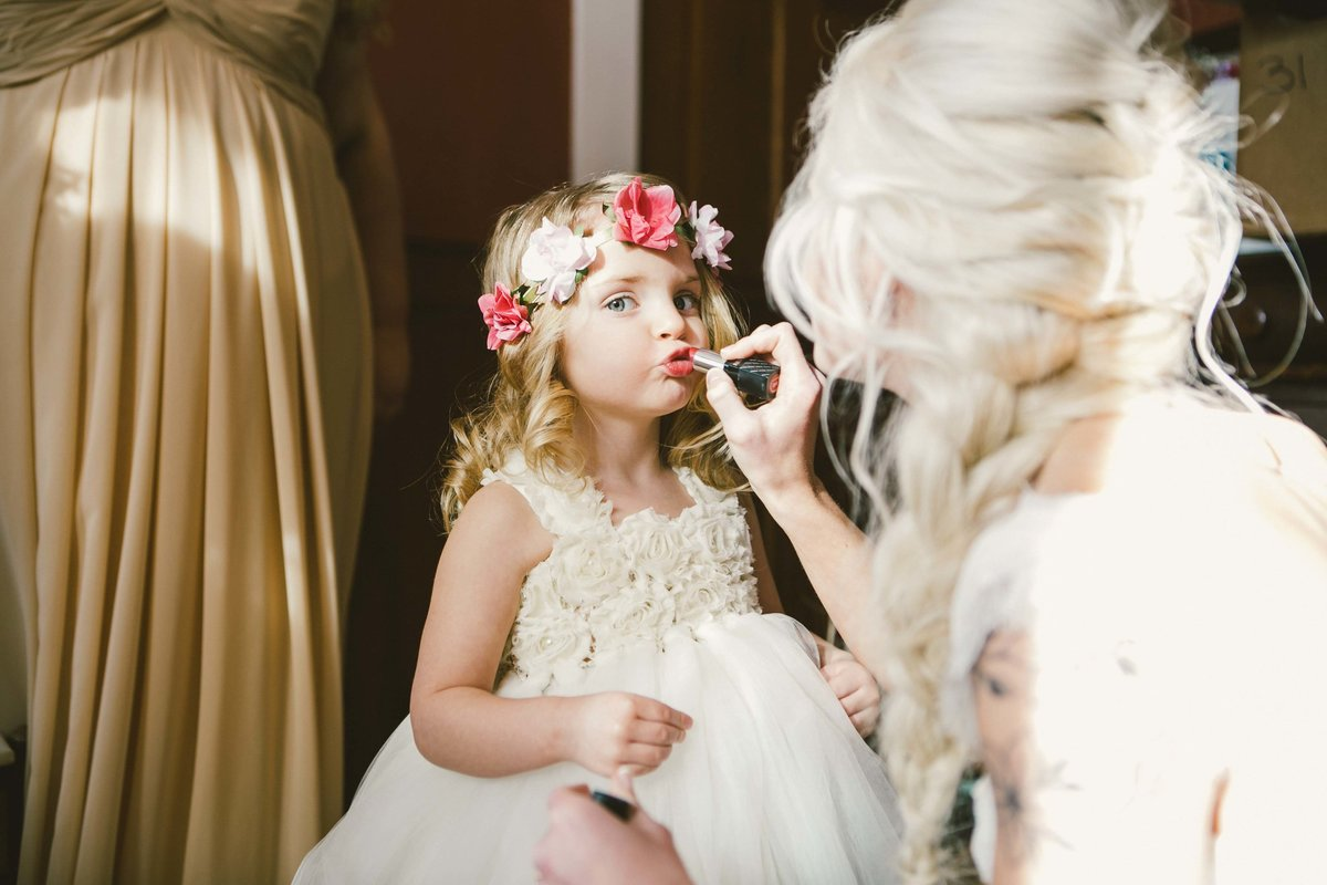 Flower girl puts on lipstick held by bride at Mustard seed garden wedding