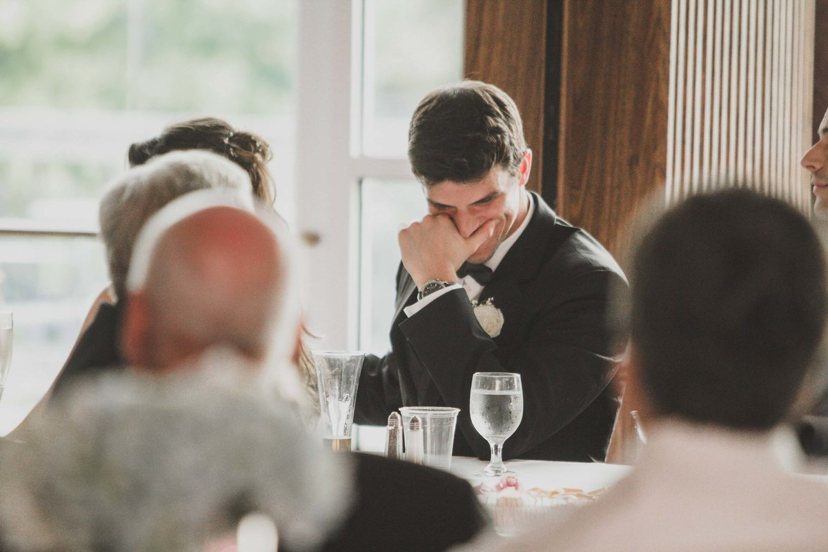 Groom laughs during best man speech at indianapolis country club wedding