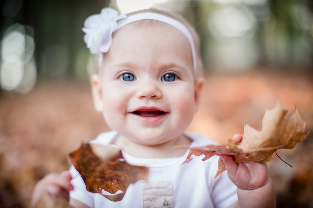 Little girl holding up leaves staring at camera at Knoxville Botanical Gardens by Knoxville Wedding Photographer, Amanda May photos.