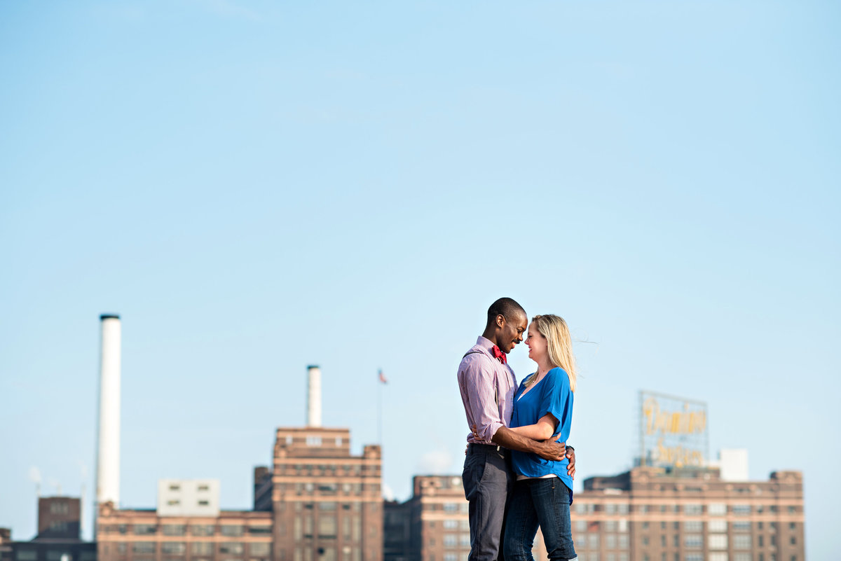 An engaged couple kiss with the Baltimore cityscape behind them.