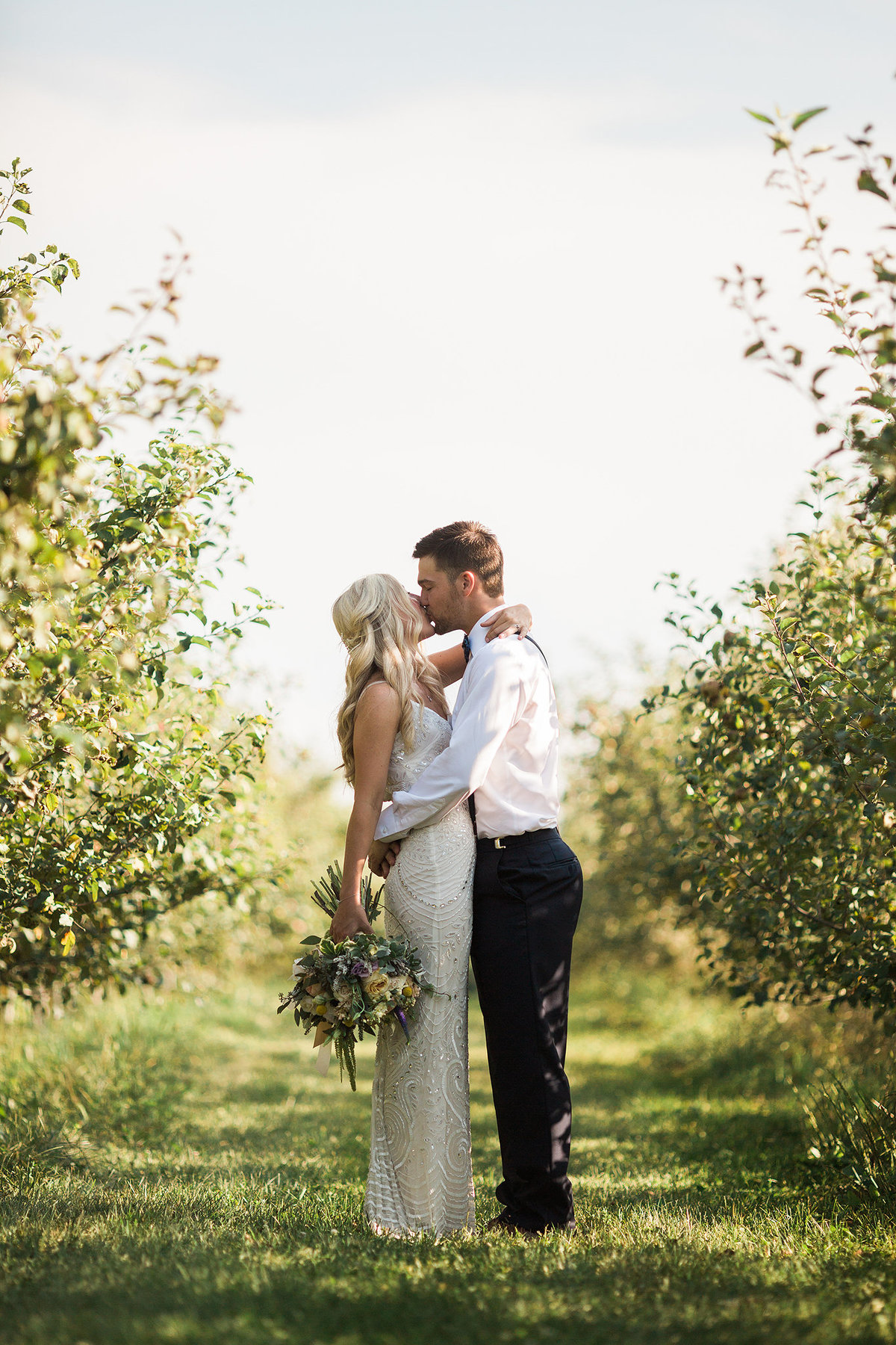 wedding couple kissing in the middle of an apple orchard