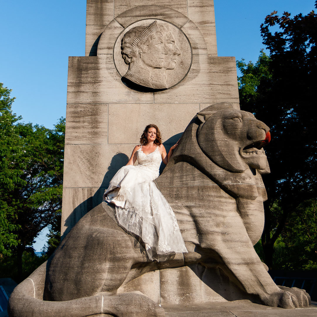 bride sitting on a stone lion located on the Toronto Lake Ontario Waterfront near Sunnyside Park