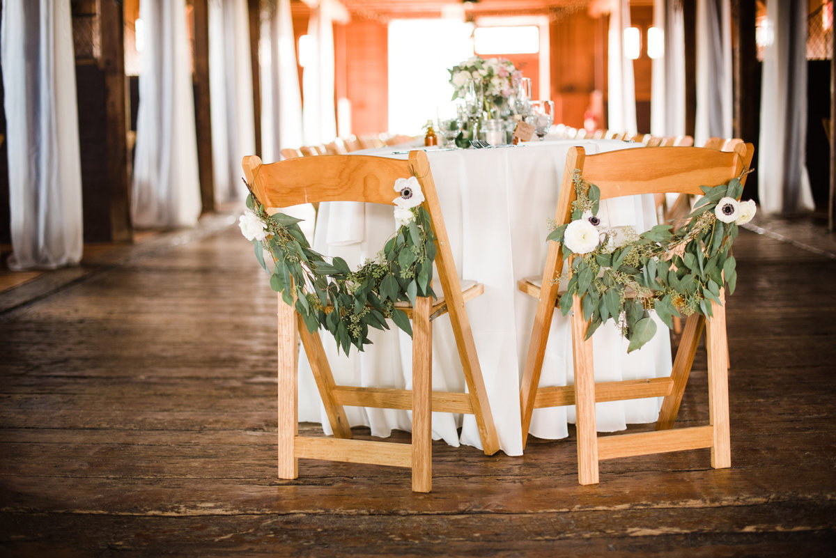 bride and groom table with greenery