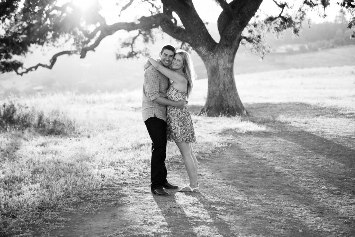 Young couple in love portraits engagement session; photography in front of tree in field