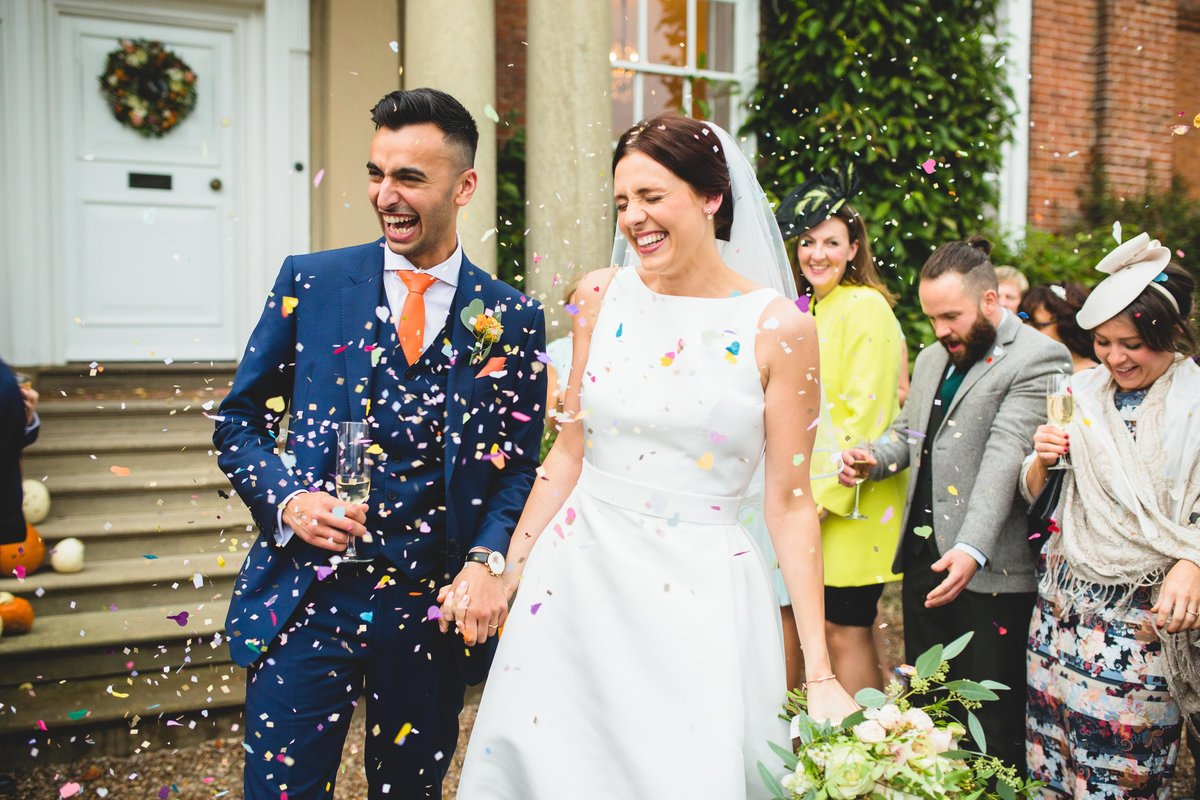 confetti being thrown at bride and groom at this autumn wedding iscoyd park