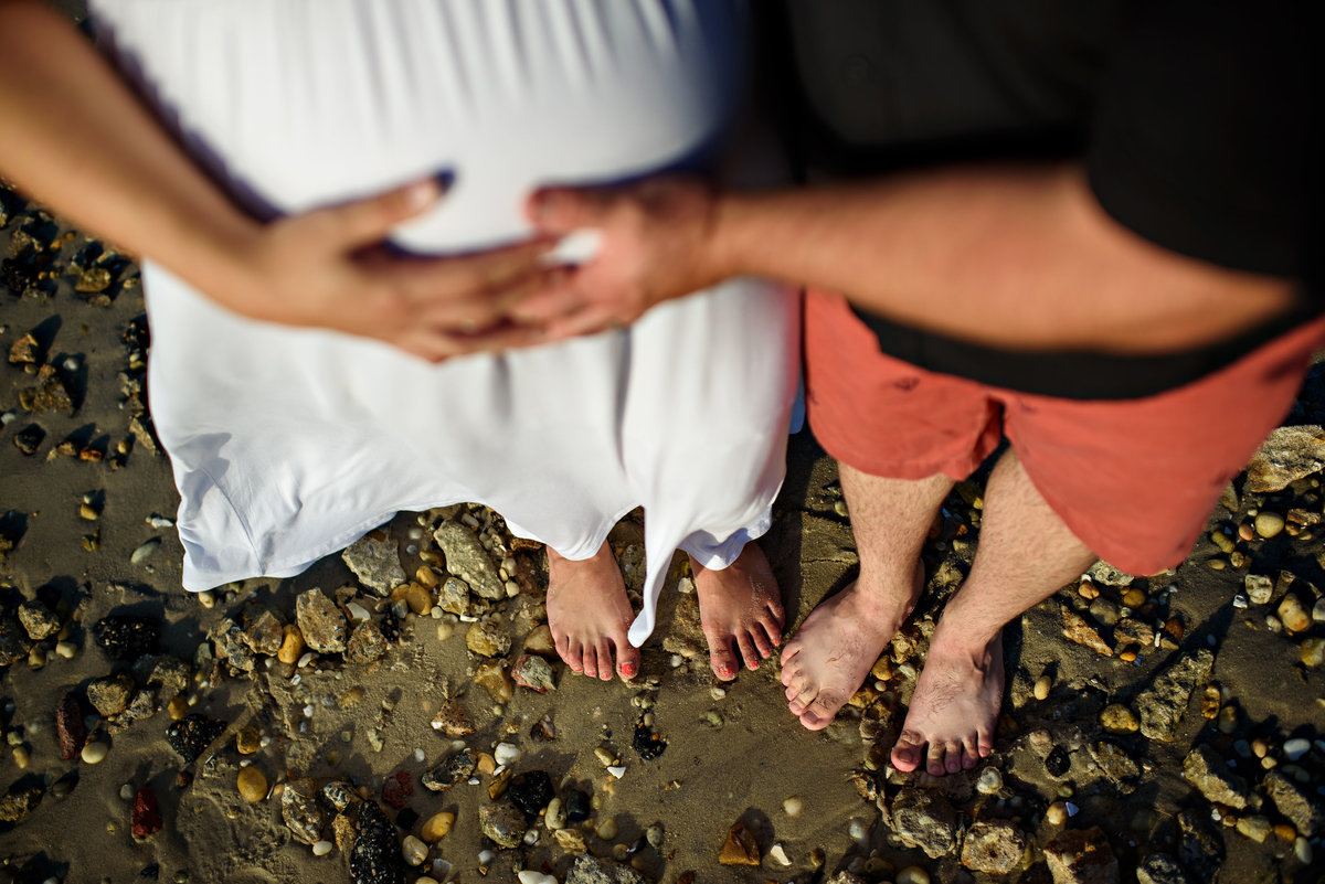 A father to be holds his wife's pregnant belly on the beach.