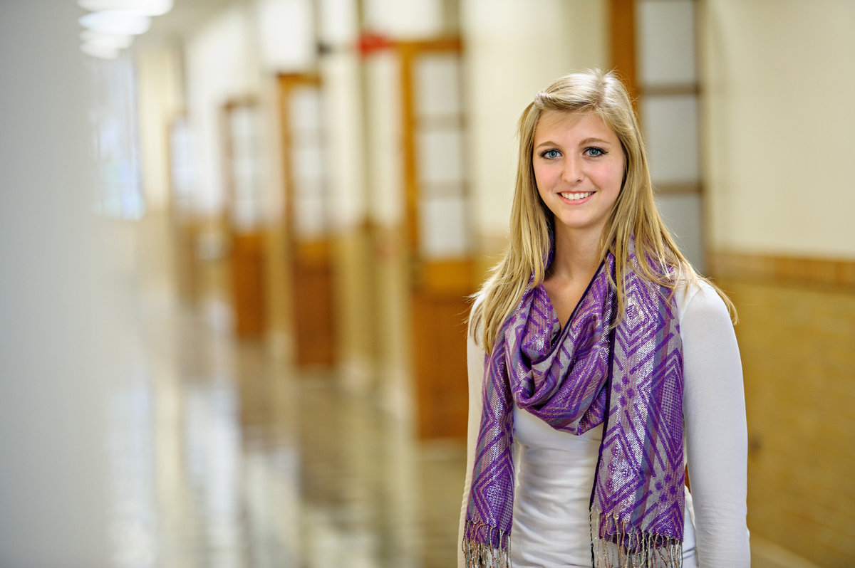 A young confident professional woman stands in a hallway of open doors.