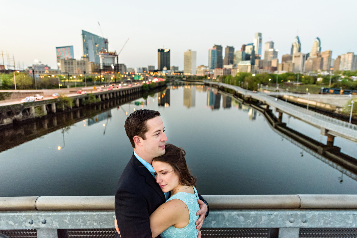 A gorgeous couple hold each other on south street bridge with the philadelphia skyline in the background.