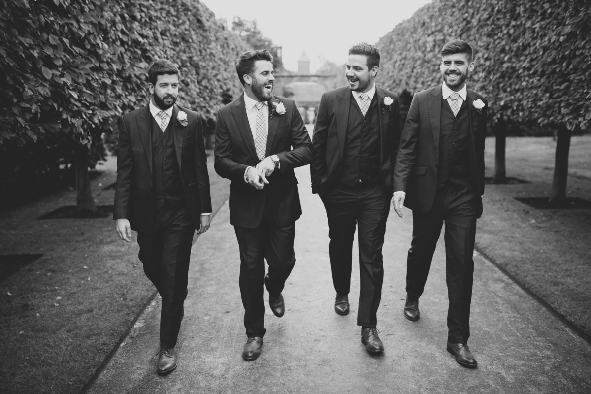 groomsmen walking and laughing before the wedding at combermere abbey