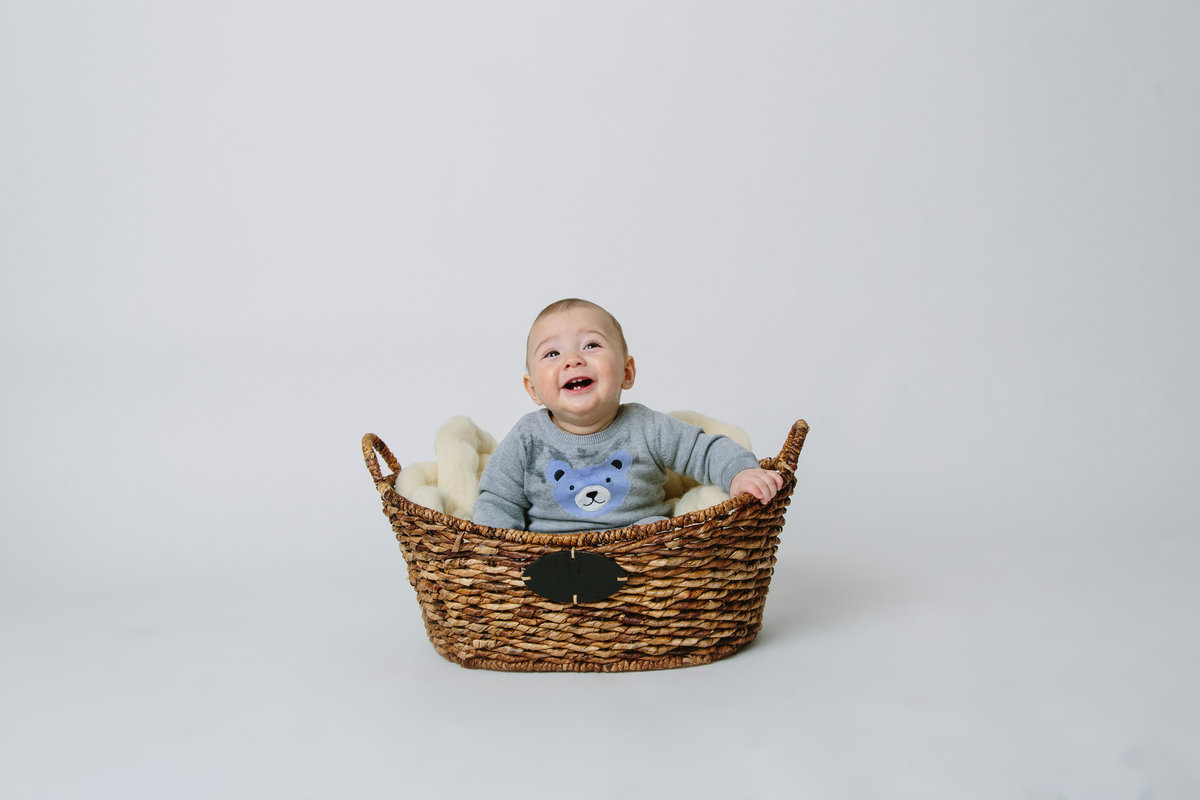 In studio photography session of baby sitting in a basket and smiling.