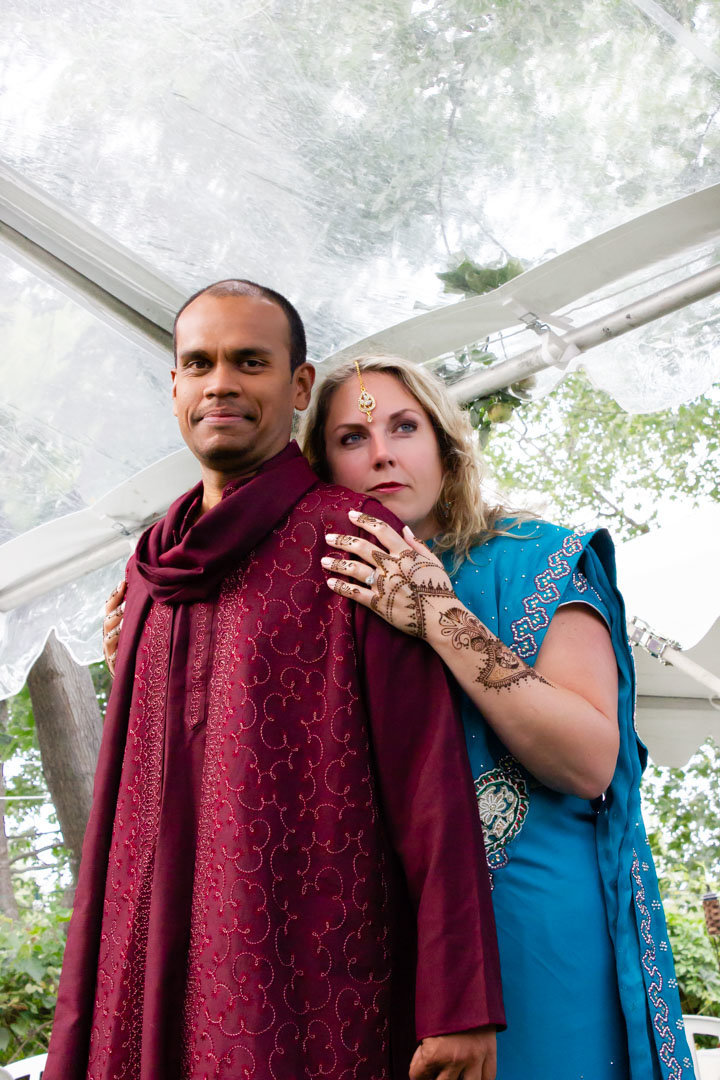bride standing behind her groom wearing a blue sari in the backyard of their home where they will be married