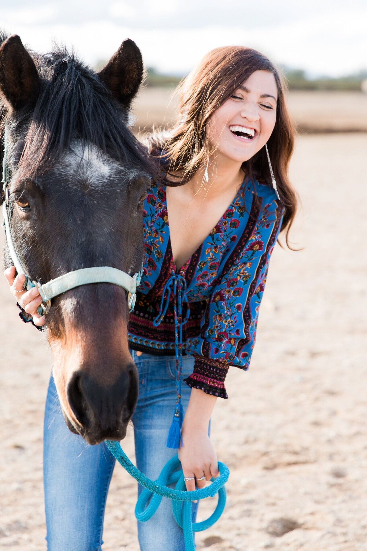 Portrait of a laughing girl standing next to her horse.