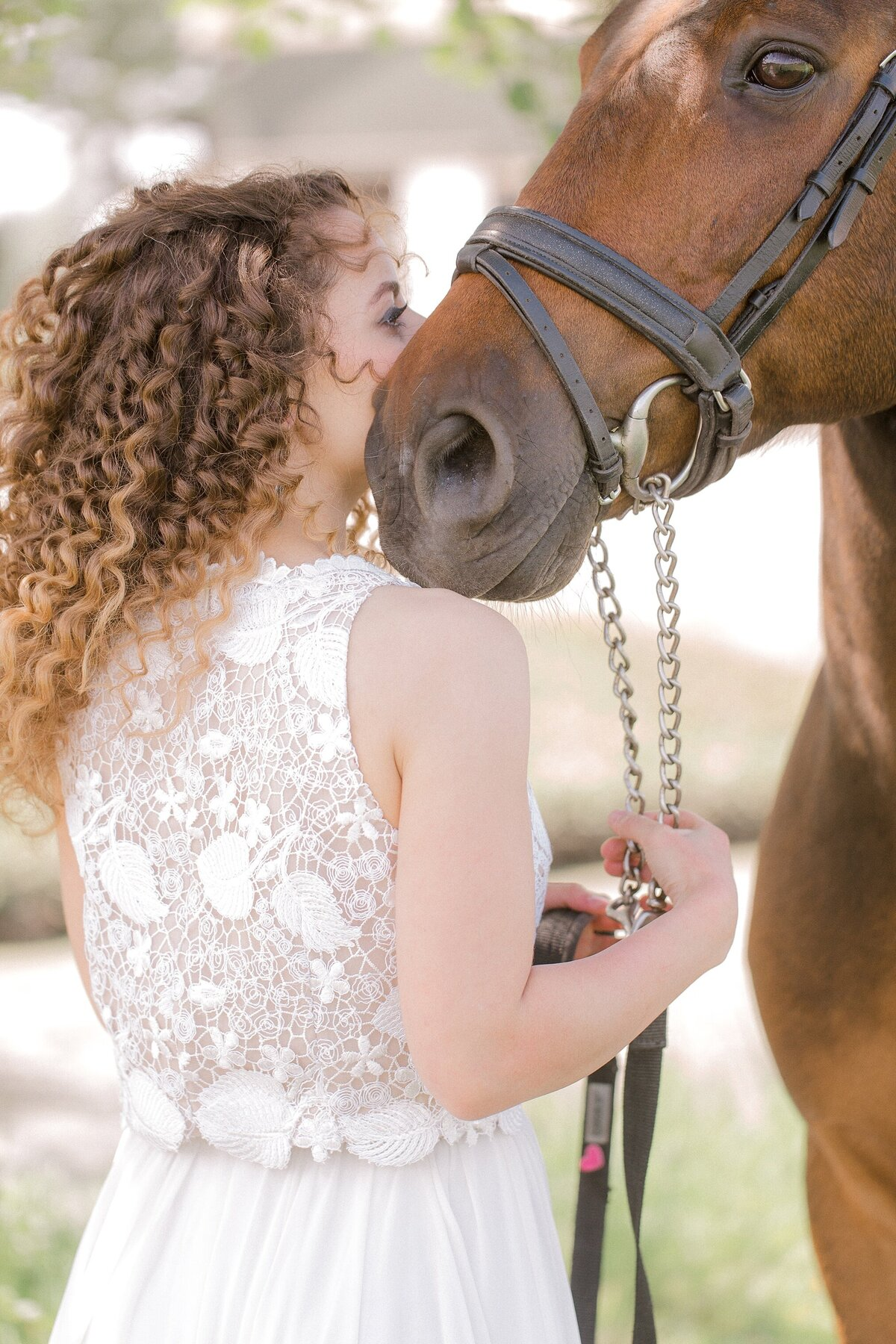 girl standing next to her horse, kissing him on the side of his nose