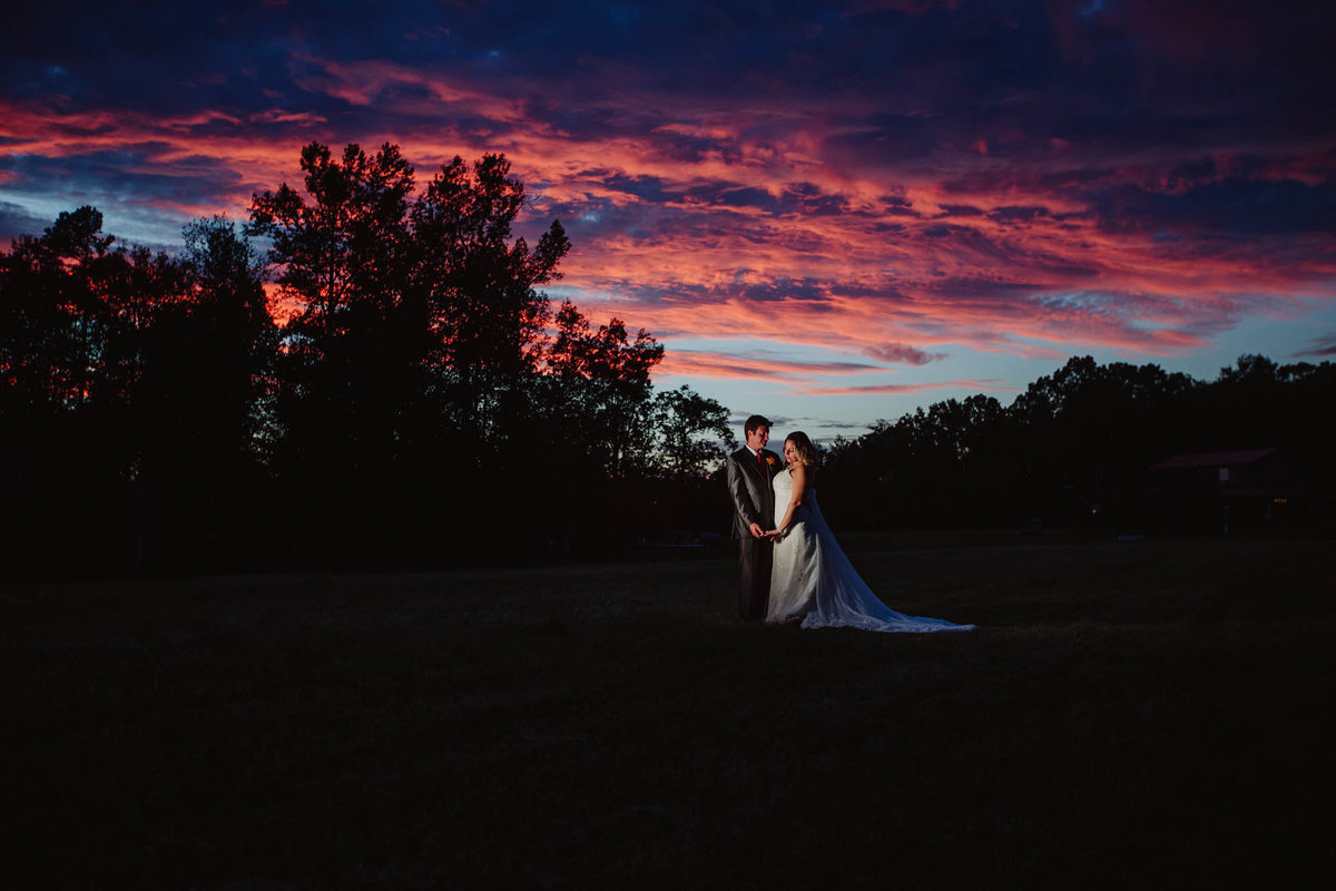 bride and groom standing in a field at sunset