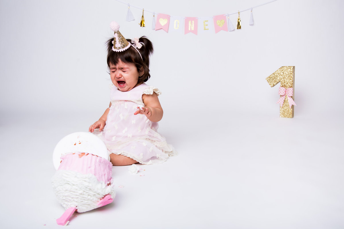 Cake smash with baby crying over cake that has fallen over in Expose The Heart Studio