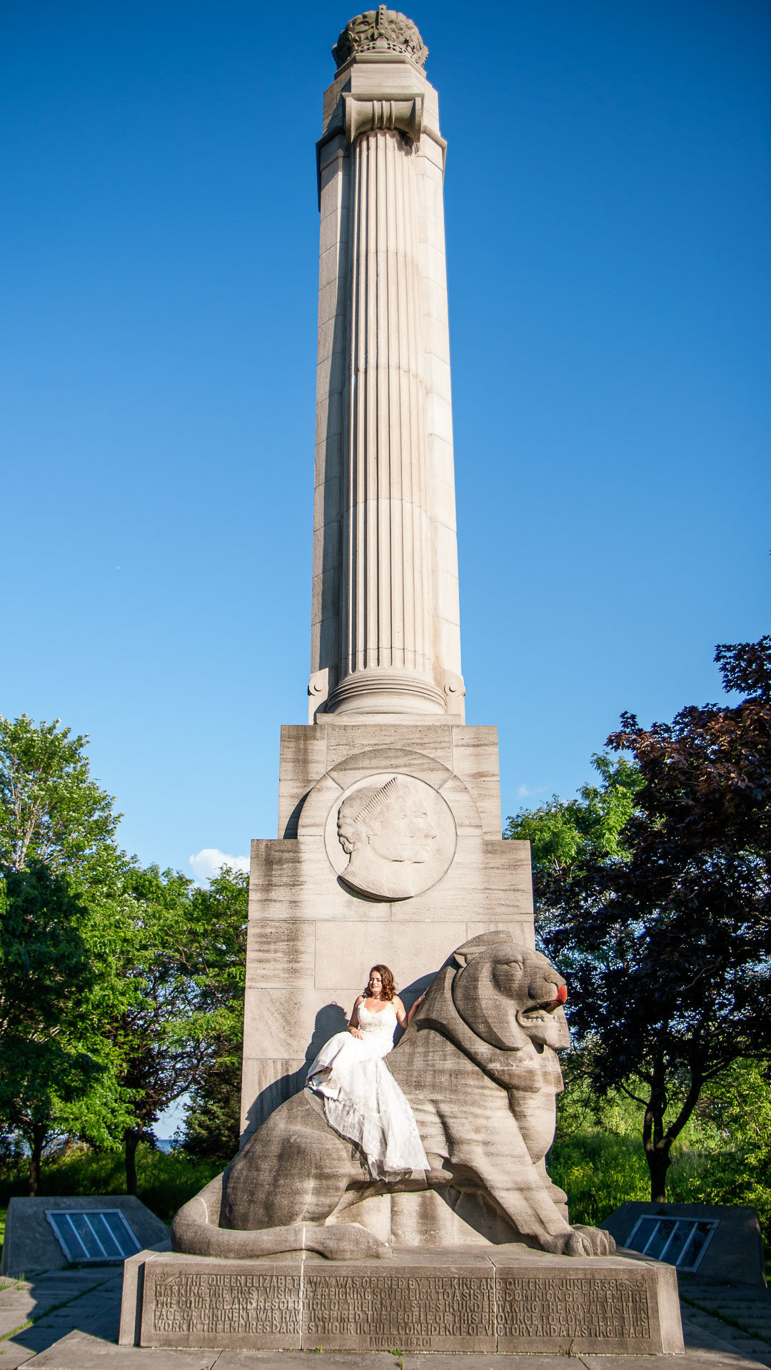 Bride sits on a lion monument at the Toronto  Lakeshore Beaches for Bridal pictures