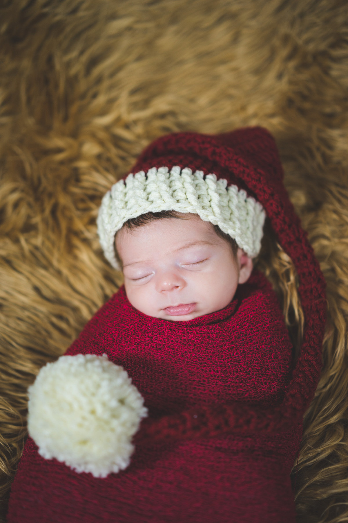 Newborn baby wrapped in red cheesecloth blanket and wearing Santa hat prop in San Antonio Photography studio.